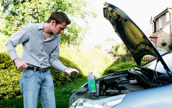 Man checking oil on his car