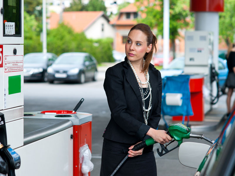 Businesswoman fills up her company car with fuel