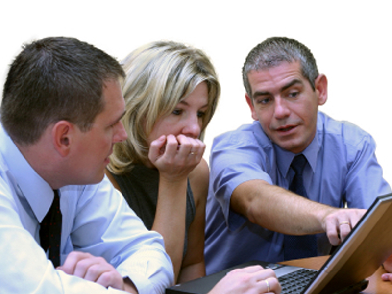 Three executives working on laptop. The main focus is on the woman, the man on the left is little soft focused.
