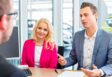 Couple arranging car finance with car dealer