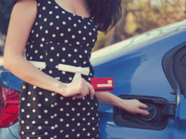 Woman with credit card about to fill up with fuel