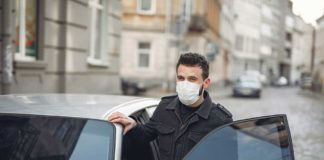 bearded man in medical mask getting out of car in street 3983438